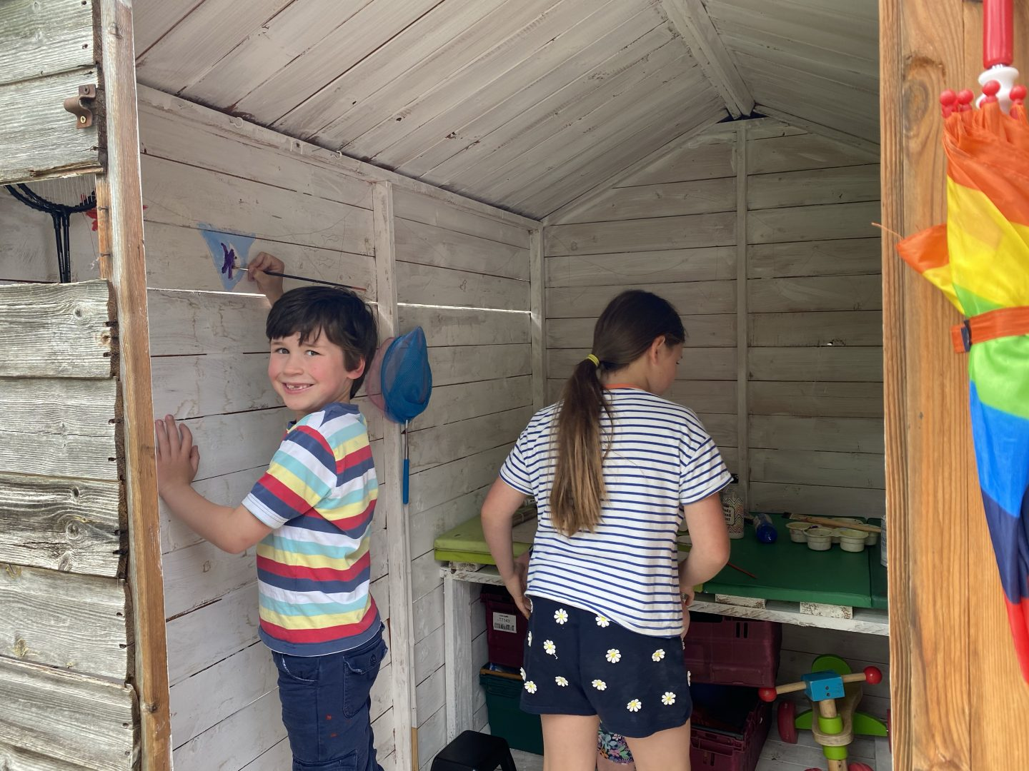 garden projects with a young boy painting a shed