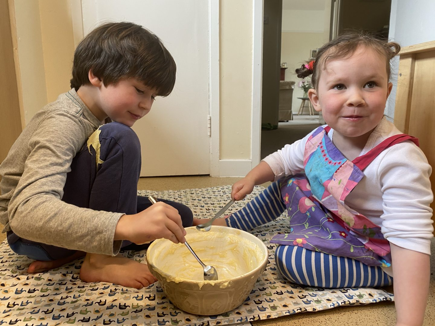 2 young children baking and  licking the bowl out