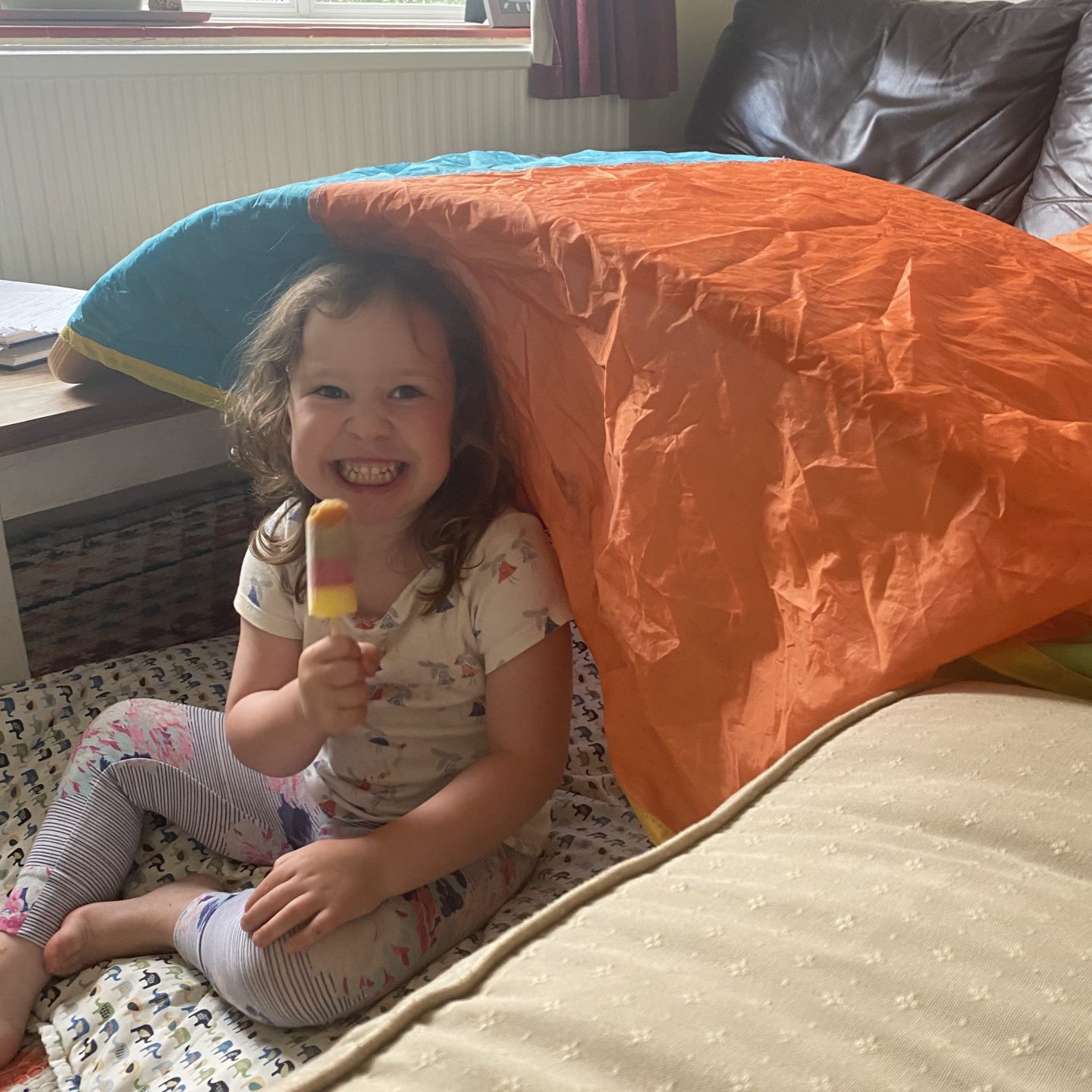 a young girl eating an ice lolly under a coloured parachute for Glasthomebury