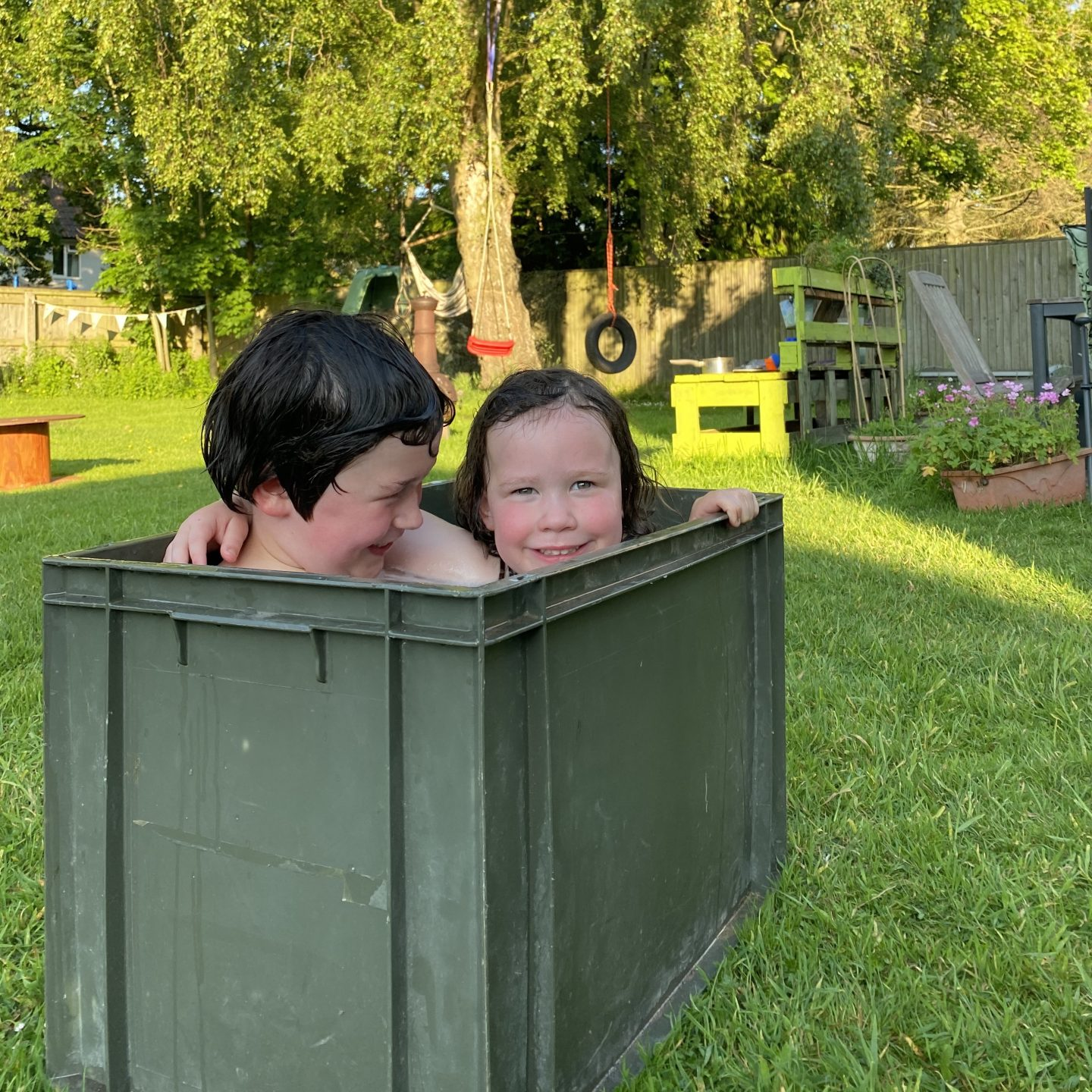 Two kids having an outdoor camping bath