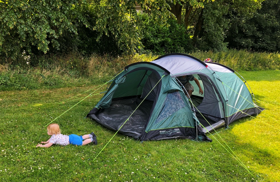 Tent and a baby playing outside