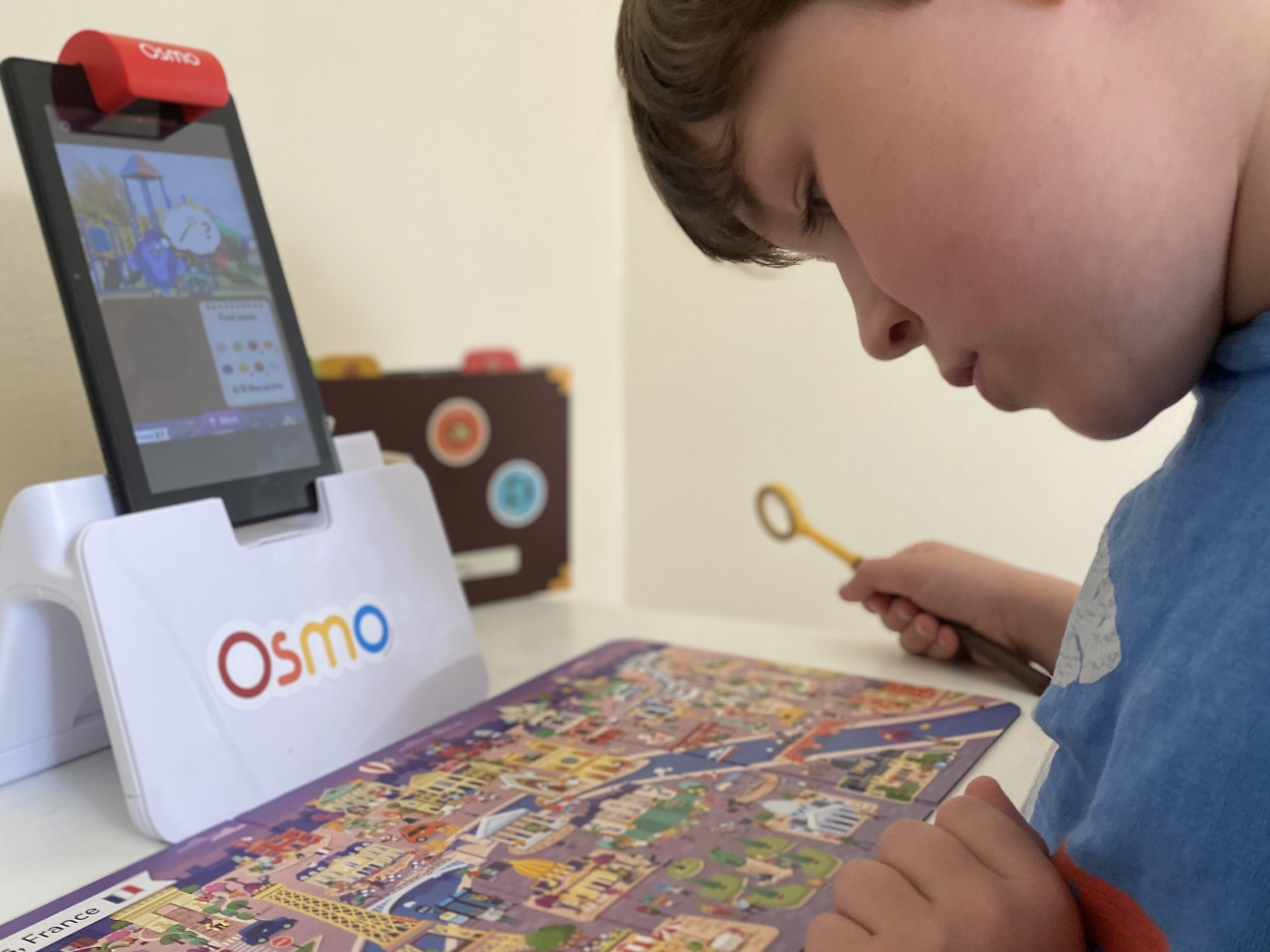 A boy using the Osmo game with a magnifying glass