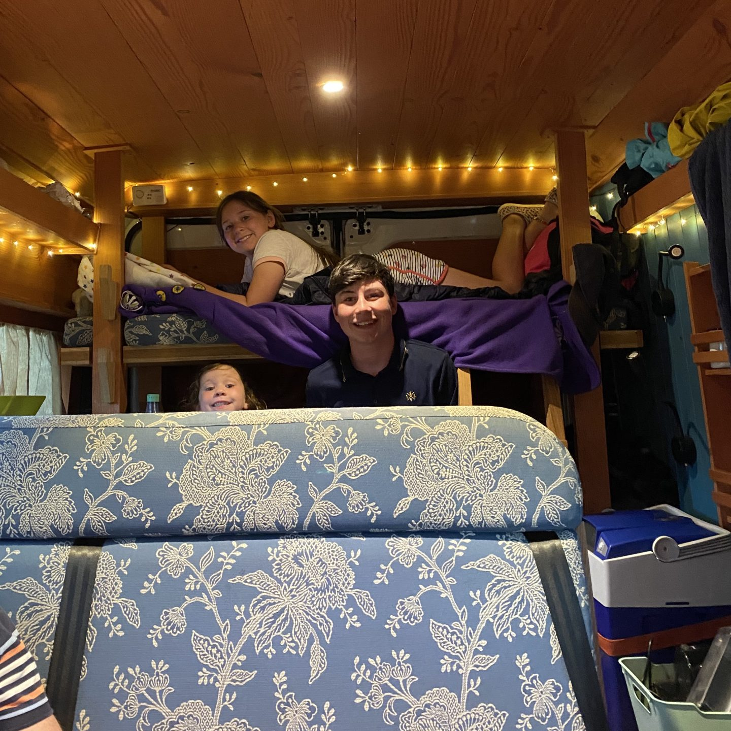 Inside a camper van with 3 children smiling