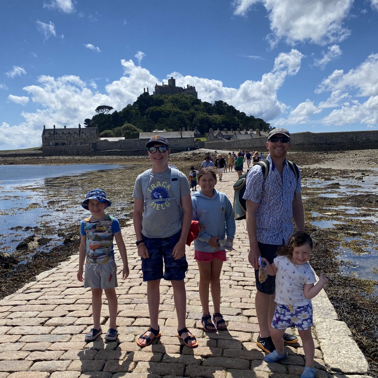 Family road trip around Devon and Cornwall St Michael's Mount with a family posing on the causeway