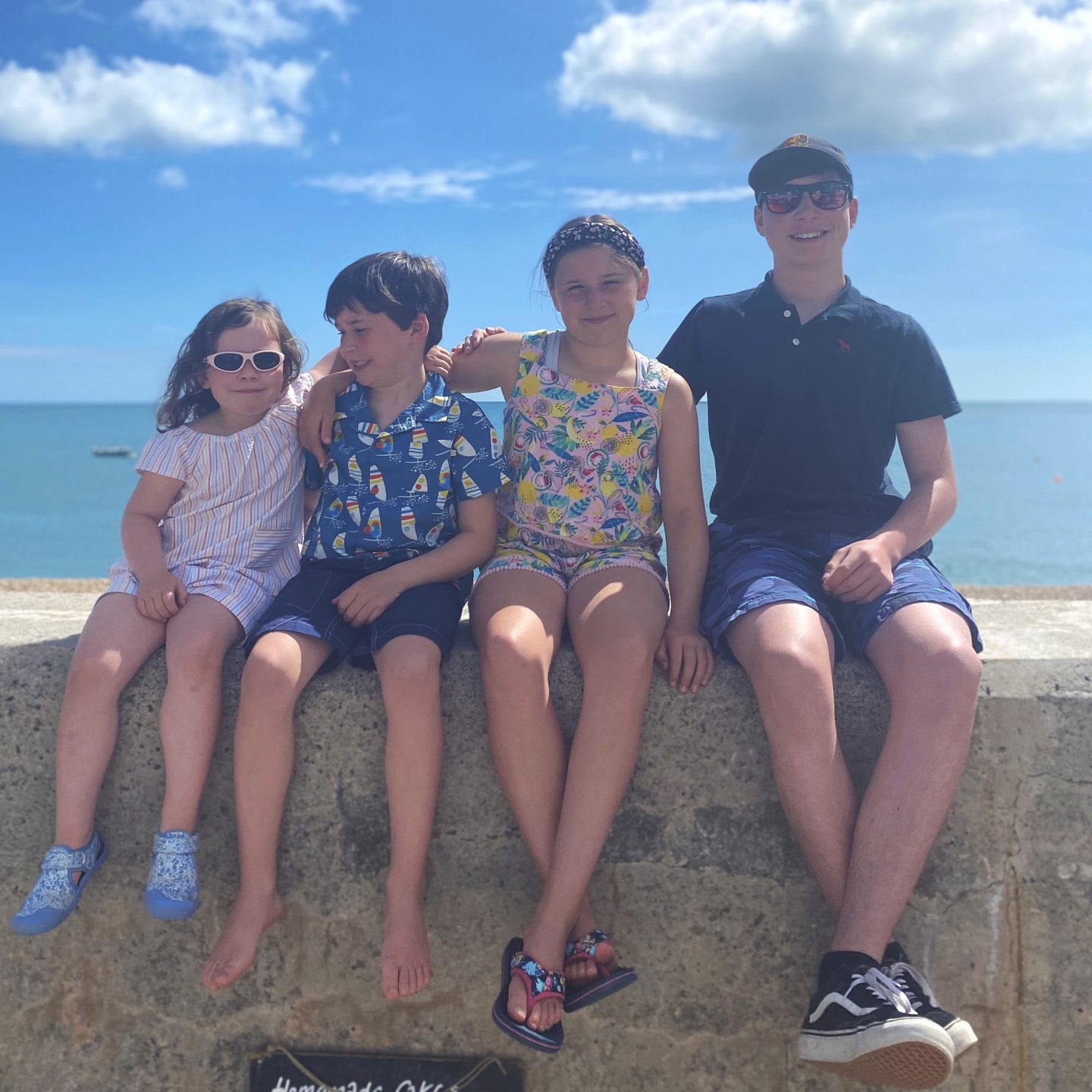 Camping in Devon  with 4 kids sat on a wall having their picture taken