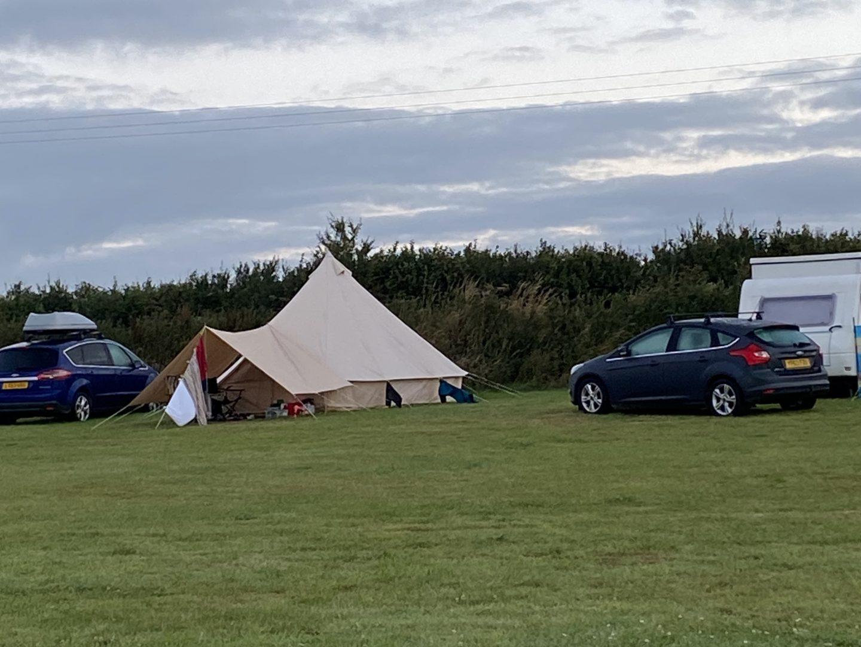 A tent and caravan in a field in Devon