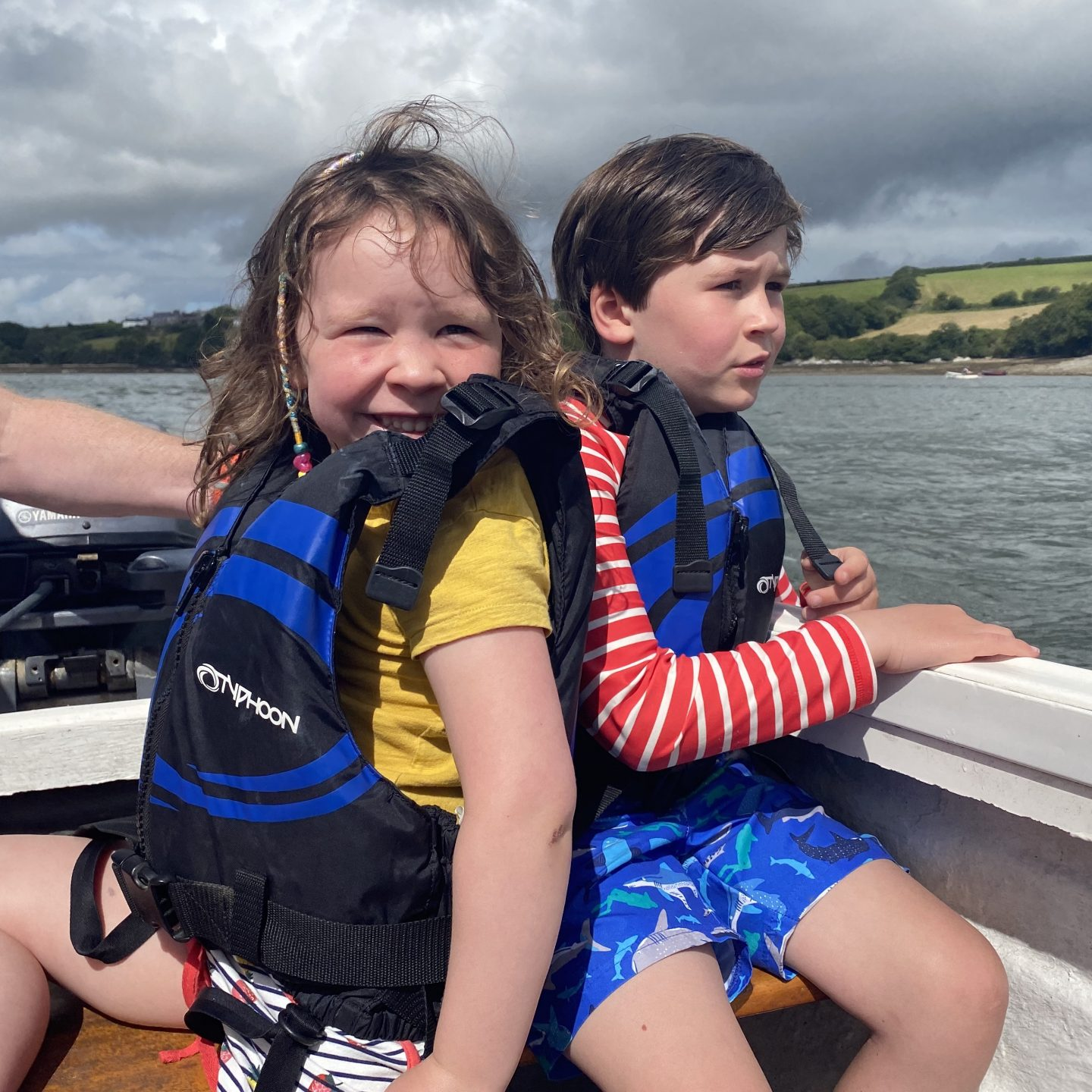A young  boy and girl sat on a boat