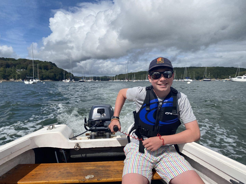 A boy driving a boat