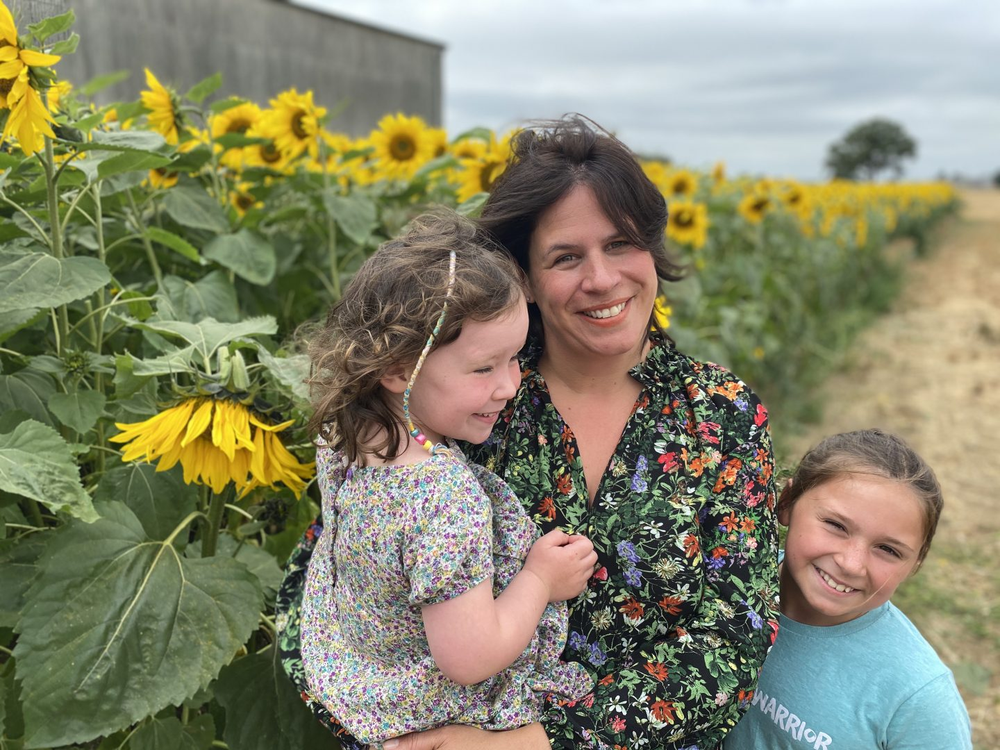 Sunflower field in Yorkshire  with a Mum and 2 girls smiling