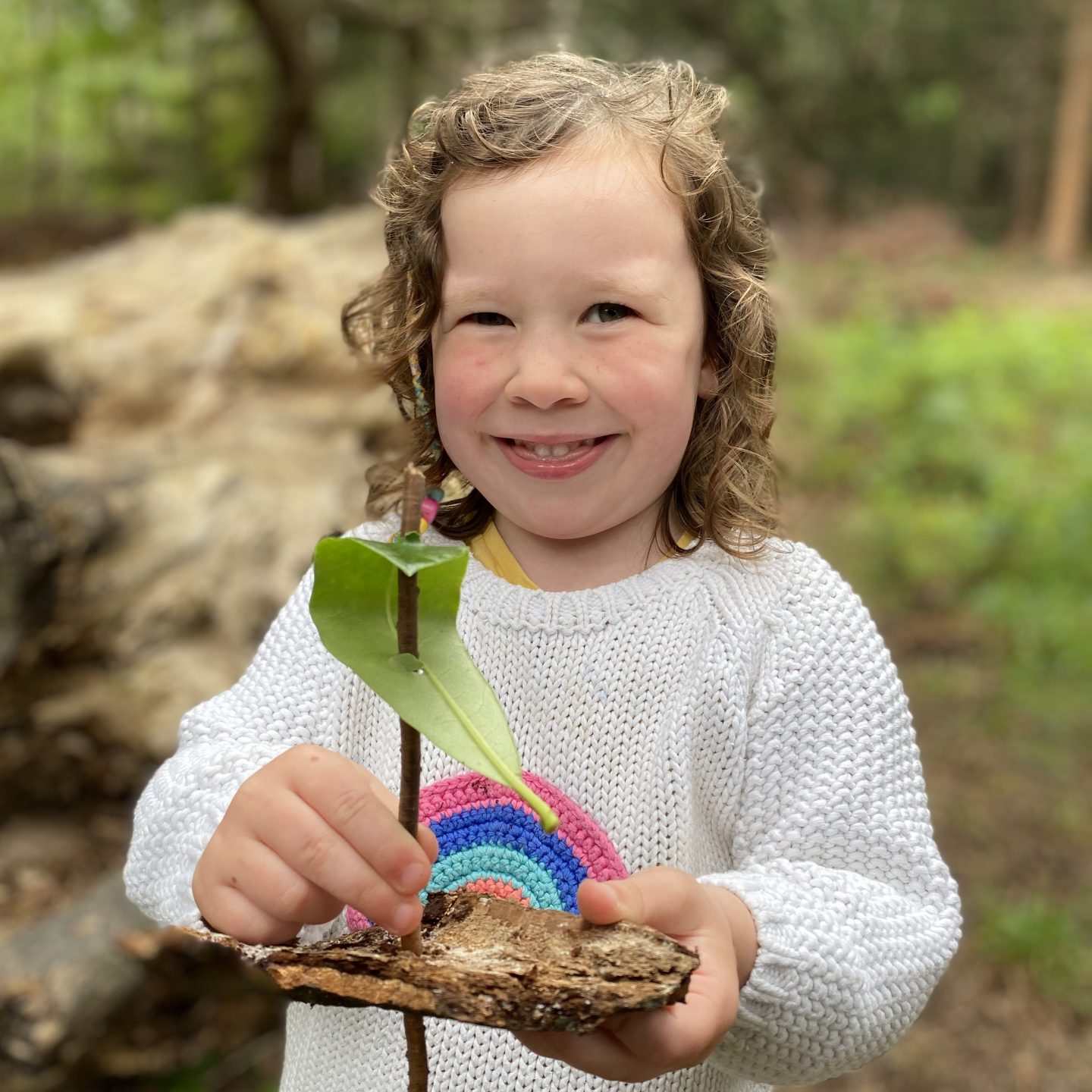 Small girl smiling with a nature boat of leaves and twigs