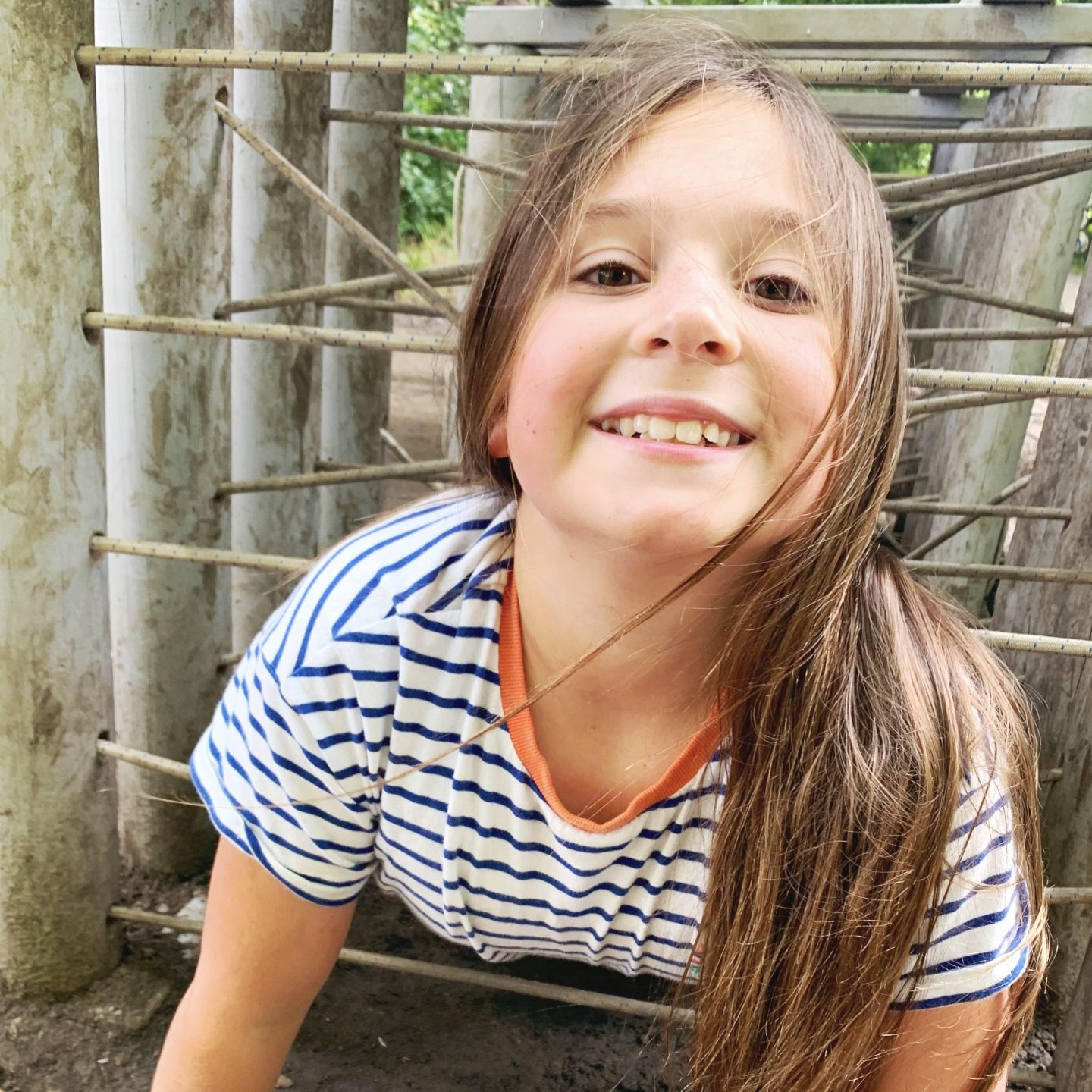 A young girl grinning at the camera on her last week of summer