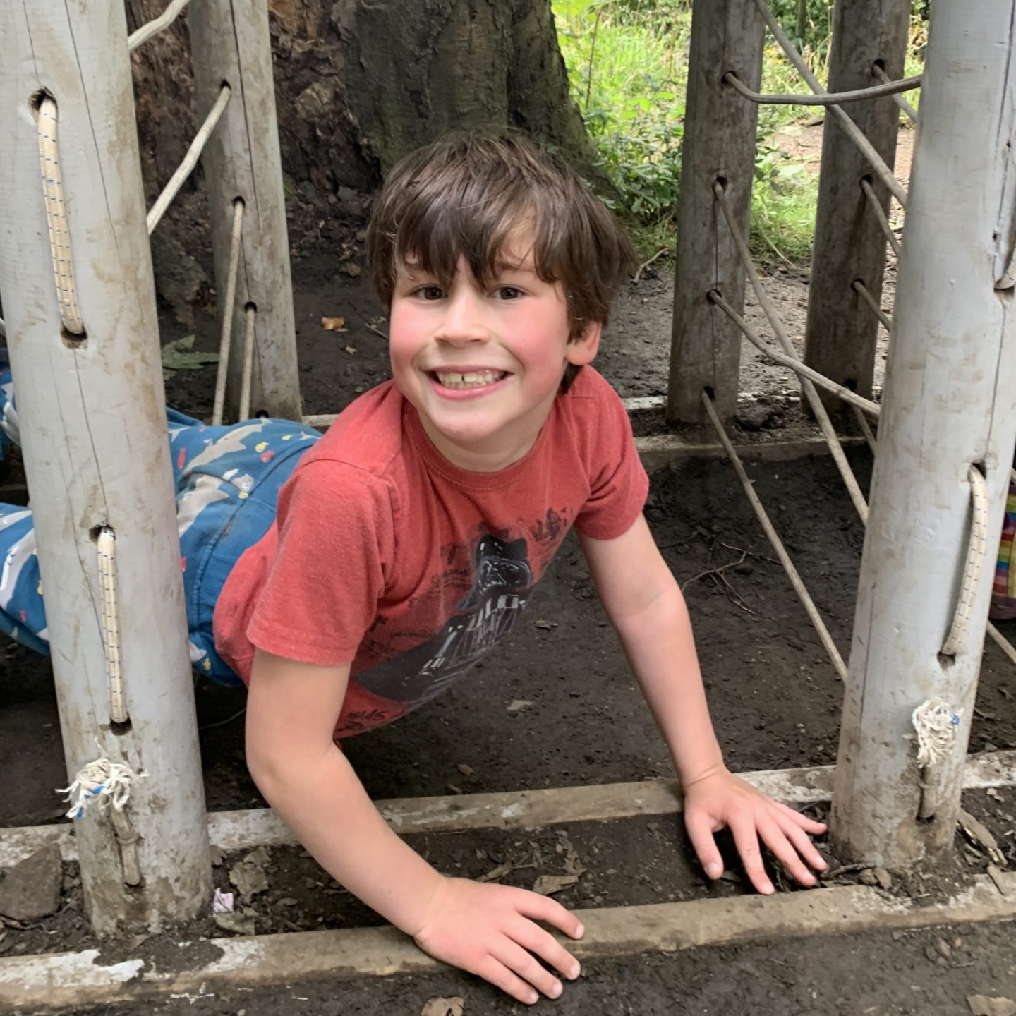 A young boy grinning on the muddy floor on the last week of Summer