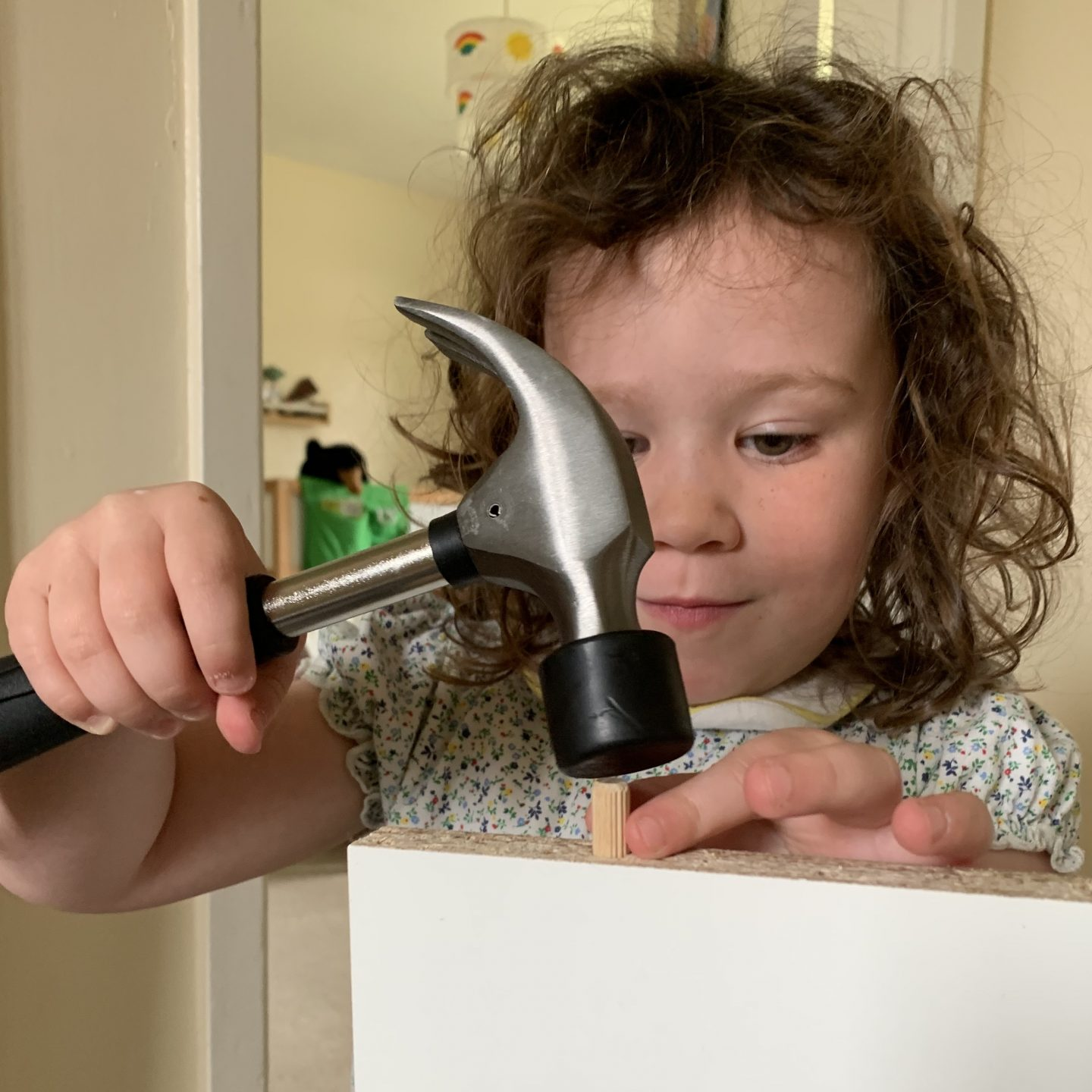 A child hammering  a nail into furniture