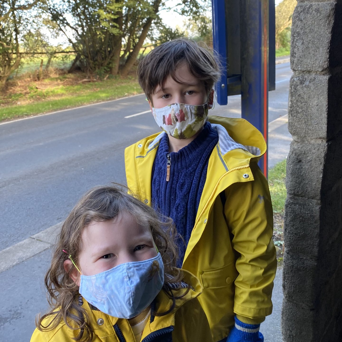 Two children stood at the bus stop wearing face masks