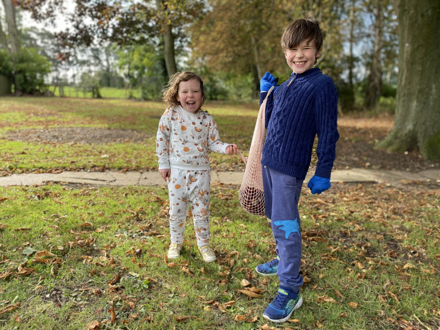 Two children carrying a bag of conkers and laughing
