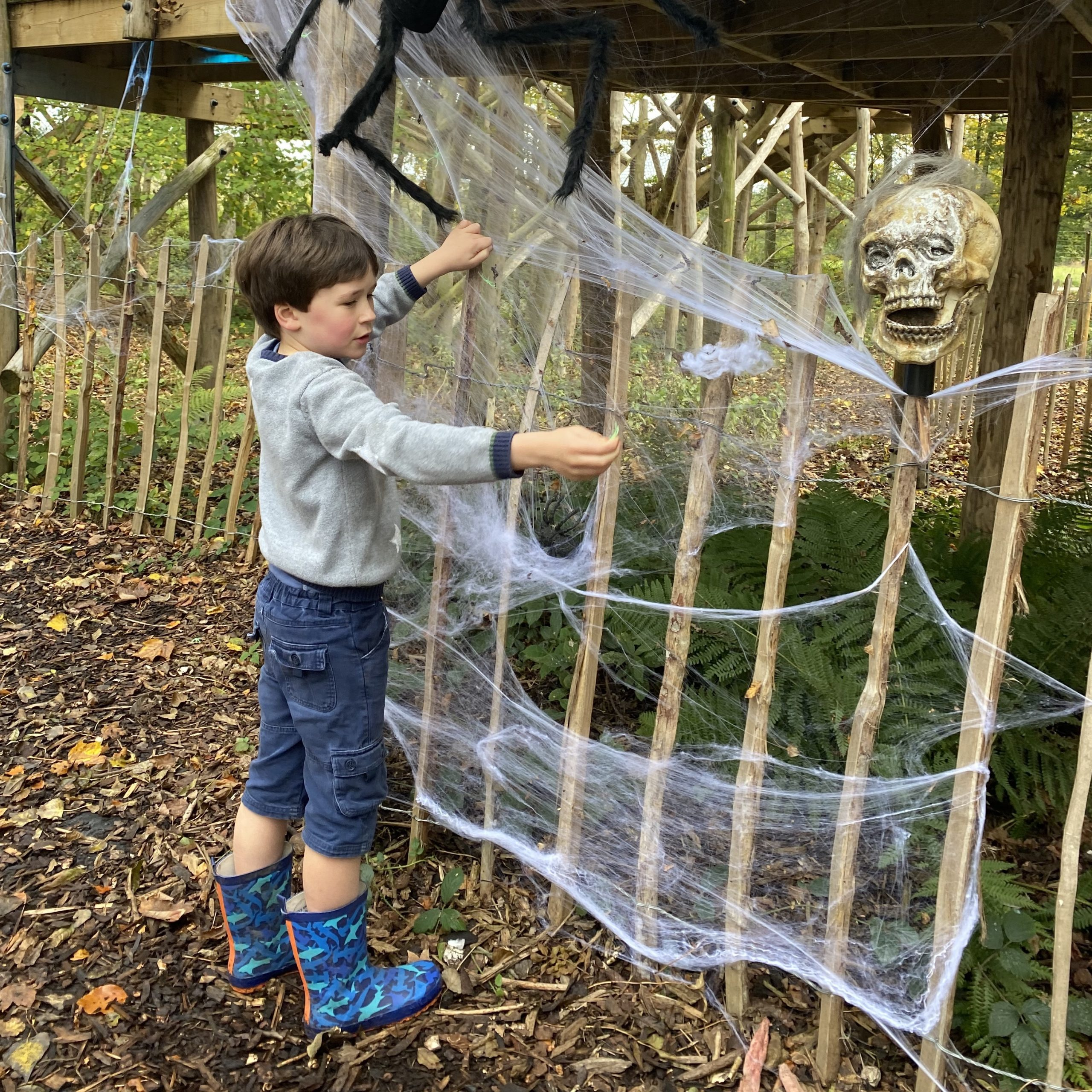 a boy playing with spooky webs on a climbing frame