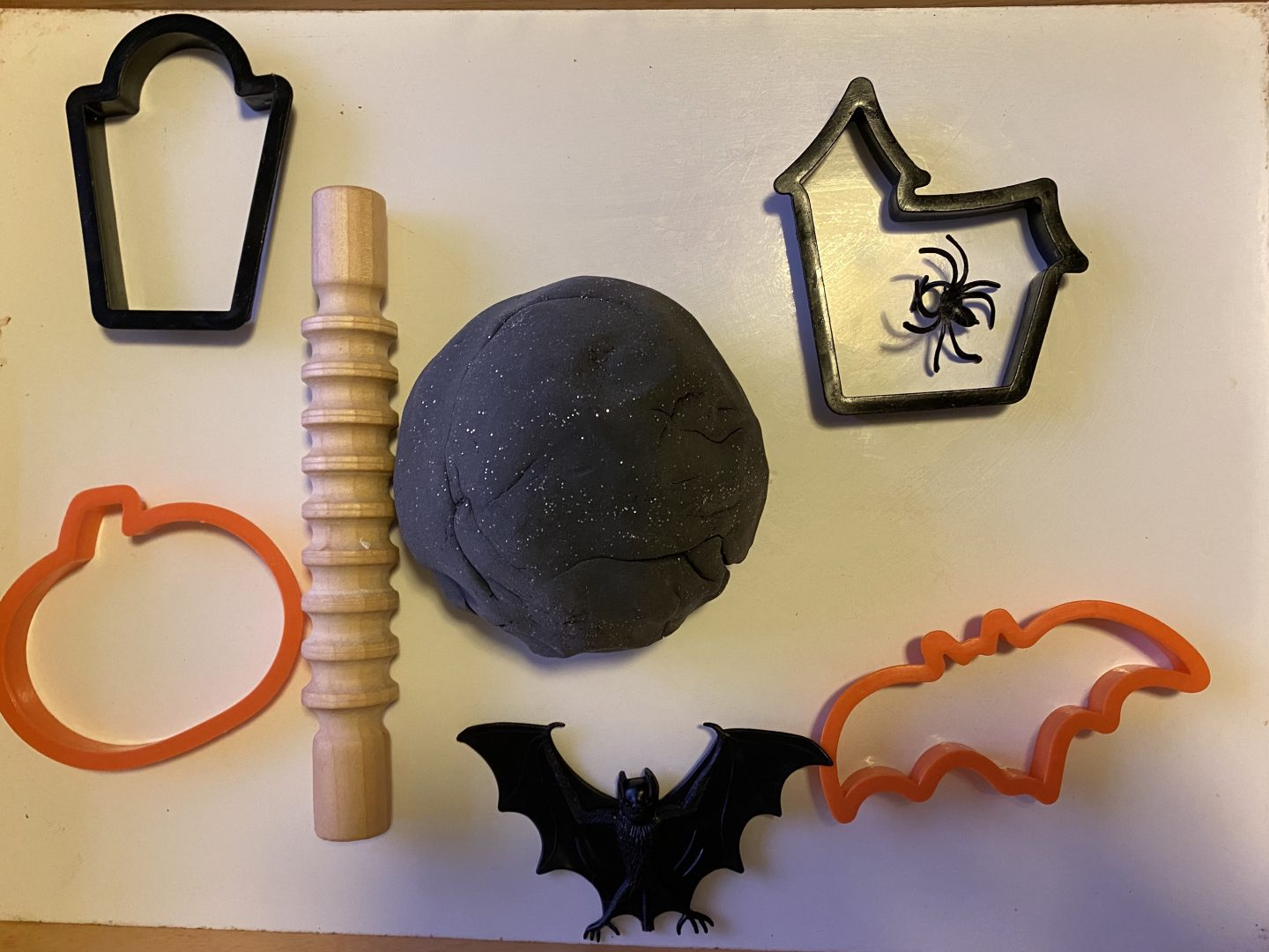 Homemade  Playdough  for Halloween with a black playdough ball and some haloween cookie cutters