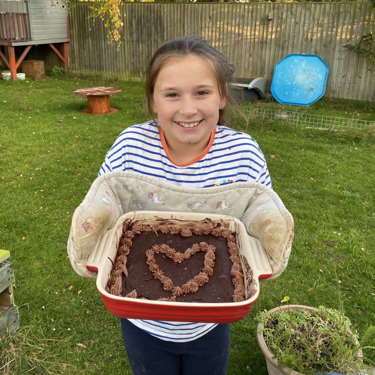A girl holding up a cake
