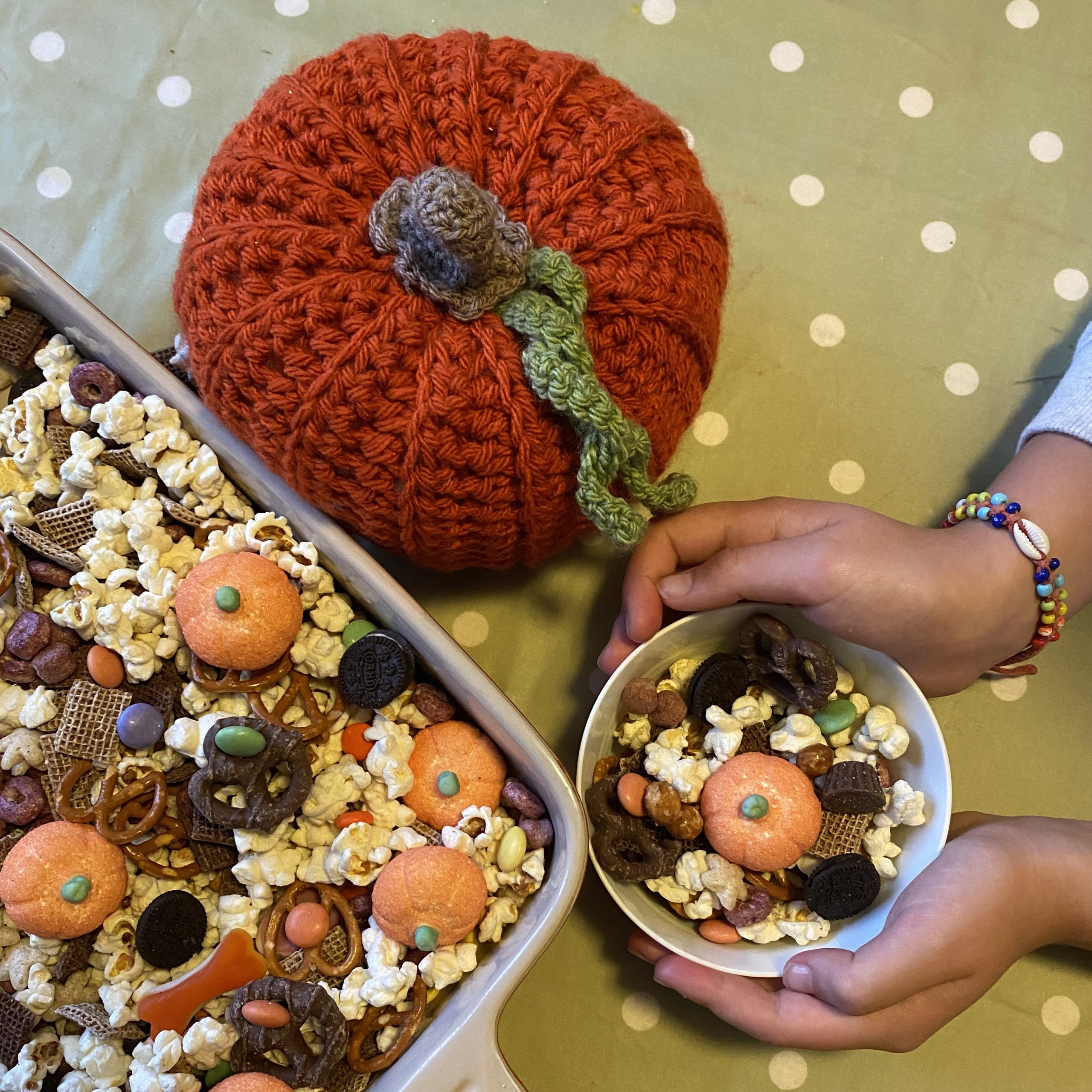 simple halloween snack mix recipe with a bowlful of treat mix next to a pumpkin