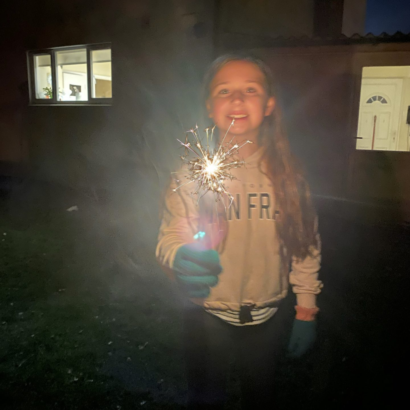 A girl holding a sparkler in the dark