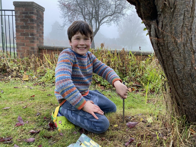 A boy planting some garden bulbs