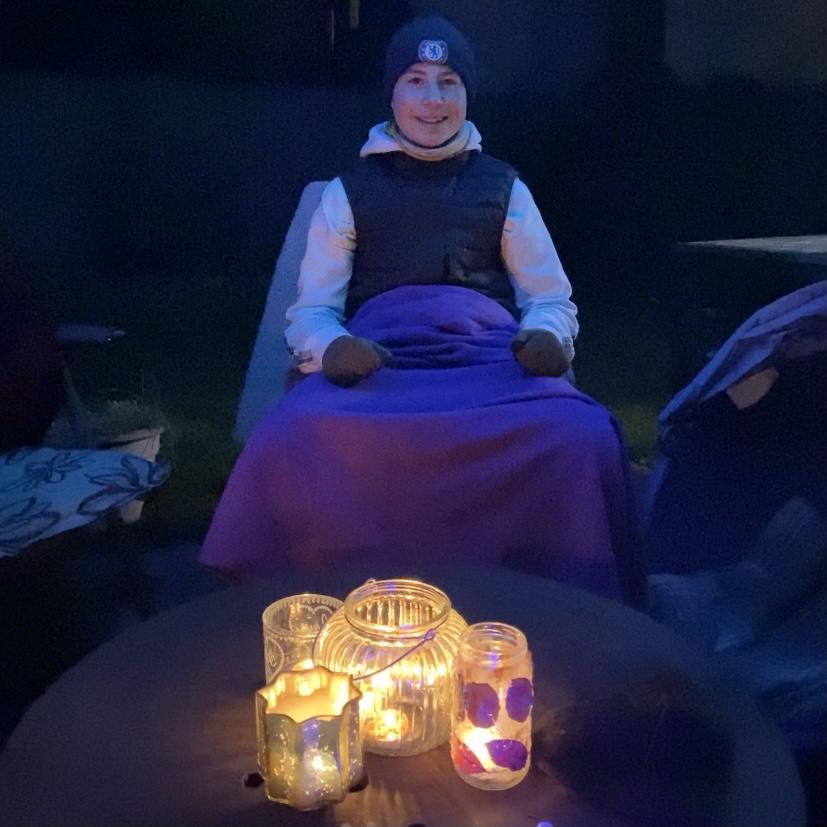 A boy sat outside round a bonfire in the dark
