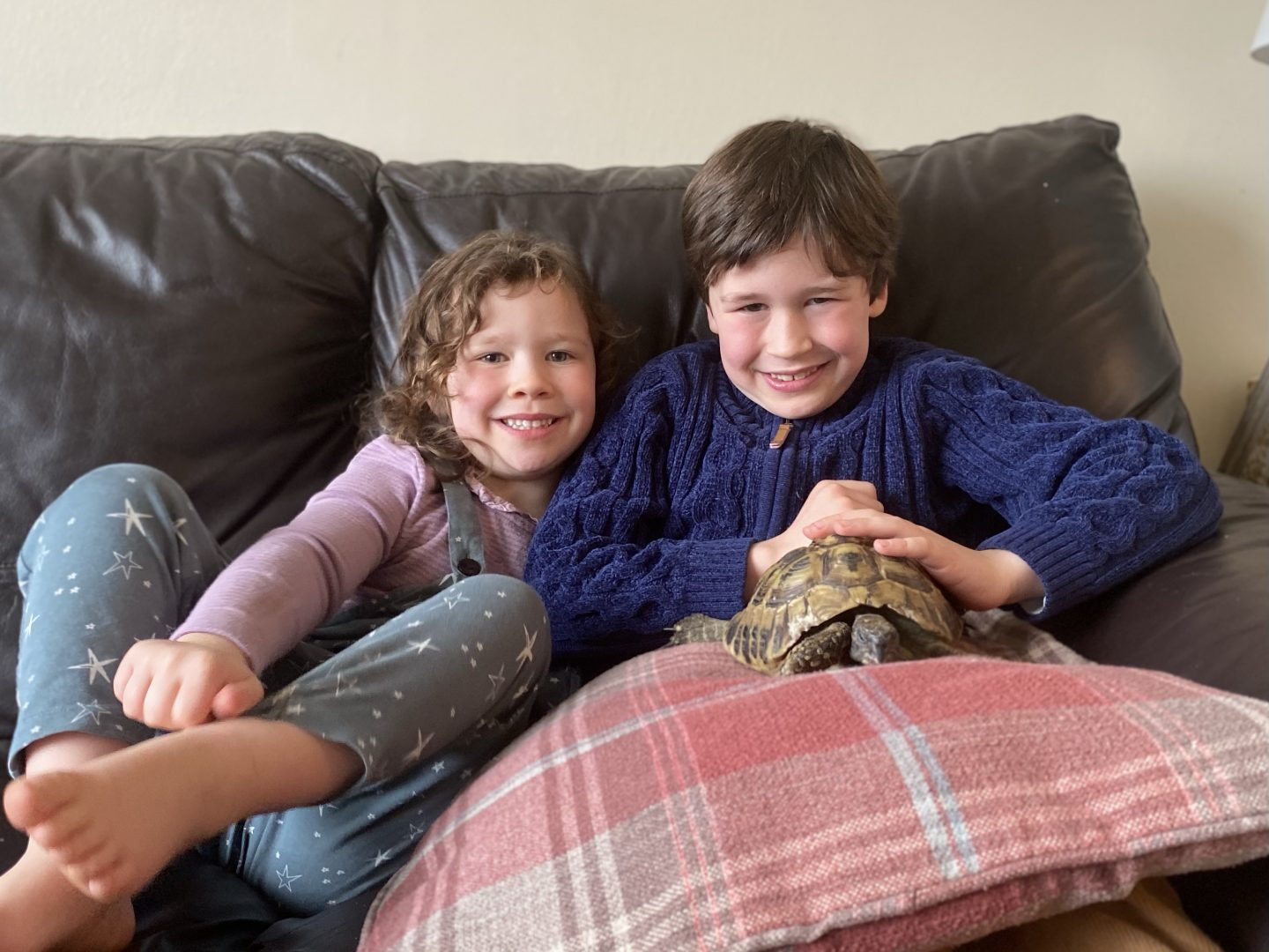 2 children with a tortoise before he goes into hibernation