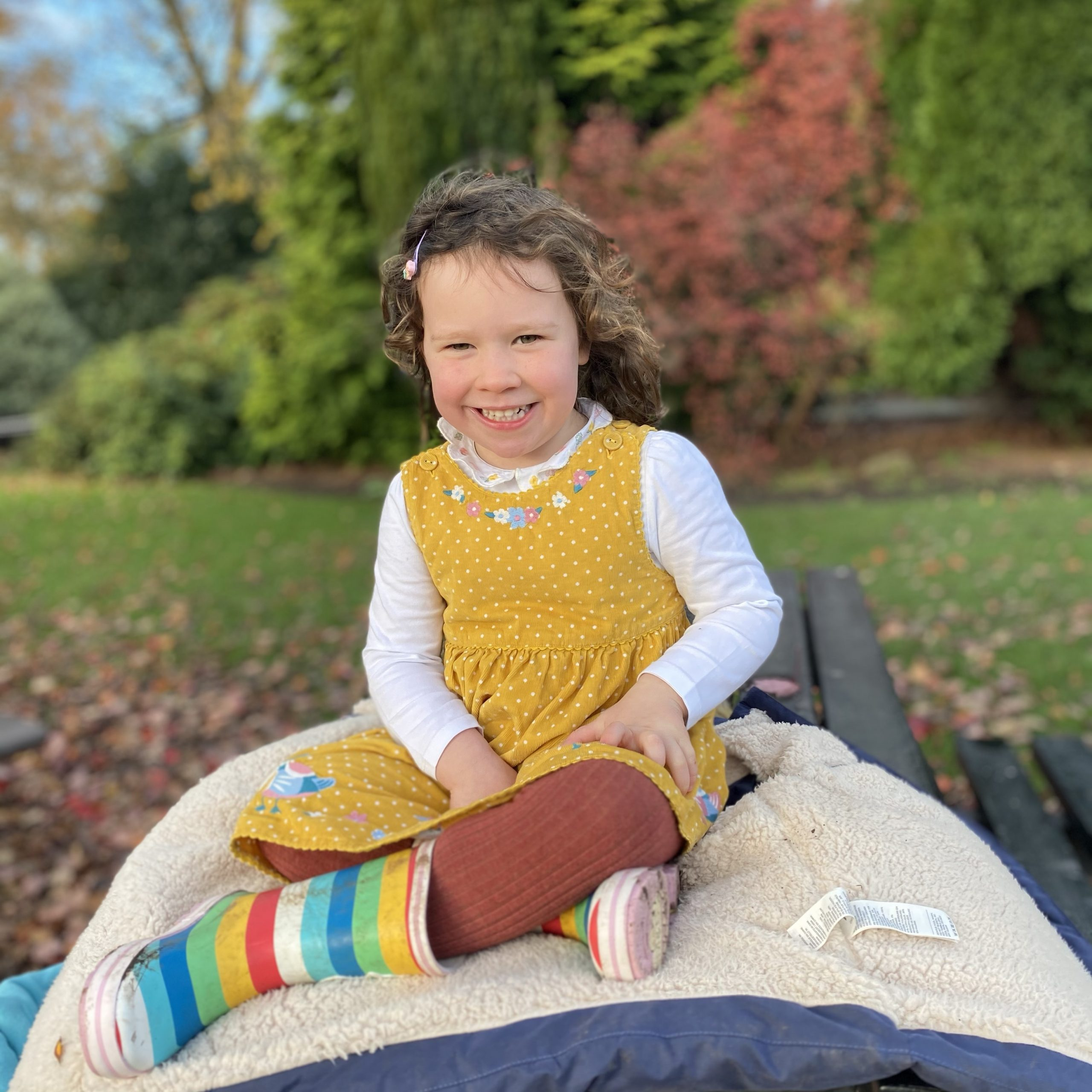 a little girl sat smiling on a picnic bench in the park