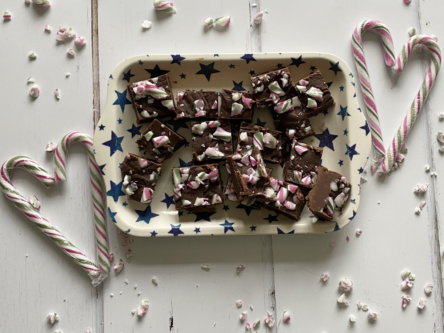 slow cooker peppermint candy cane fudge on a plate with candy cane hearts