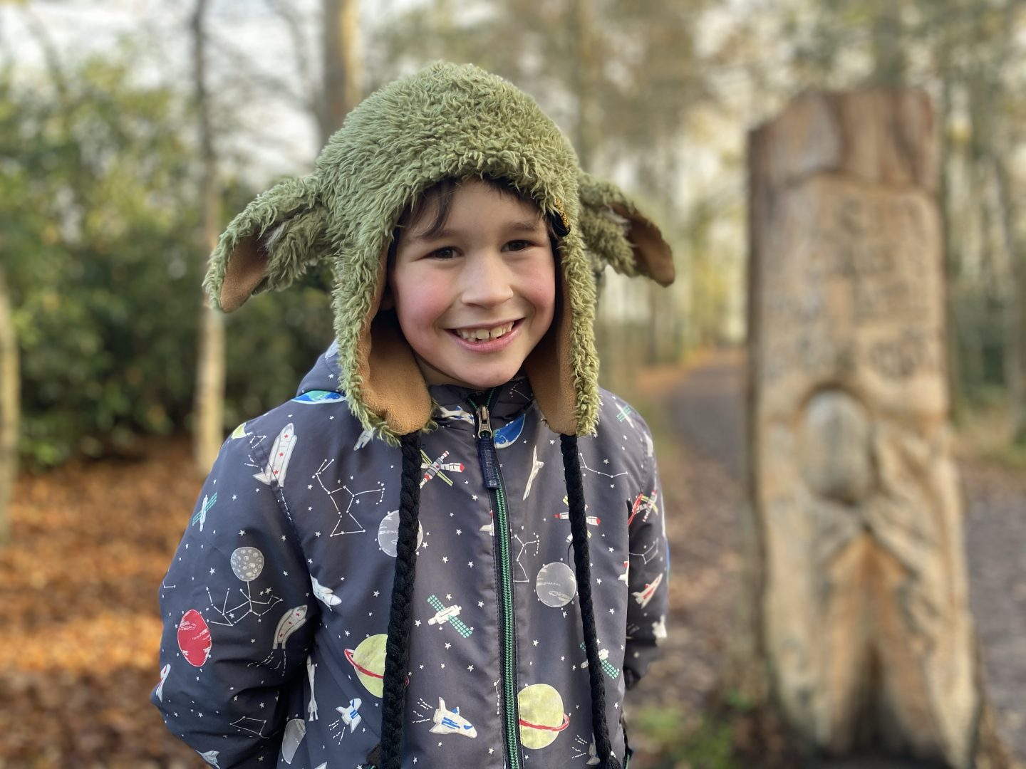 Inset day fun on a woodland walk. A young boy smiling for a picture in the woods