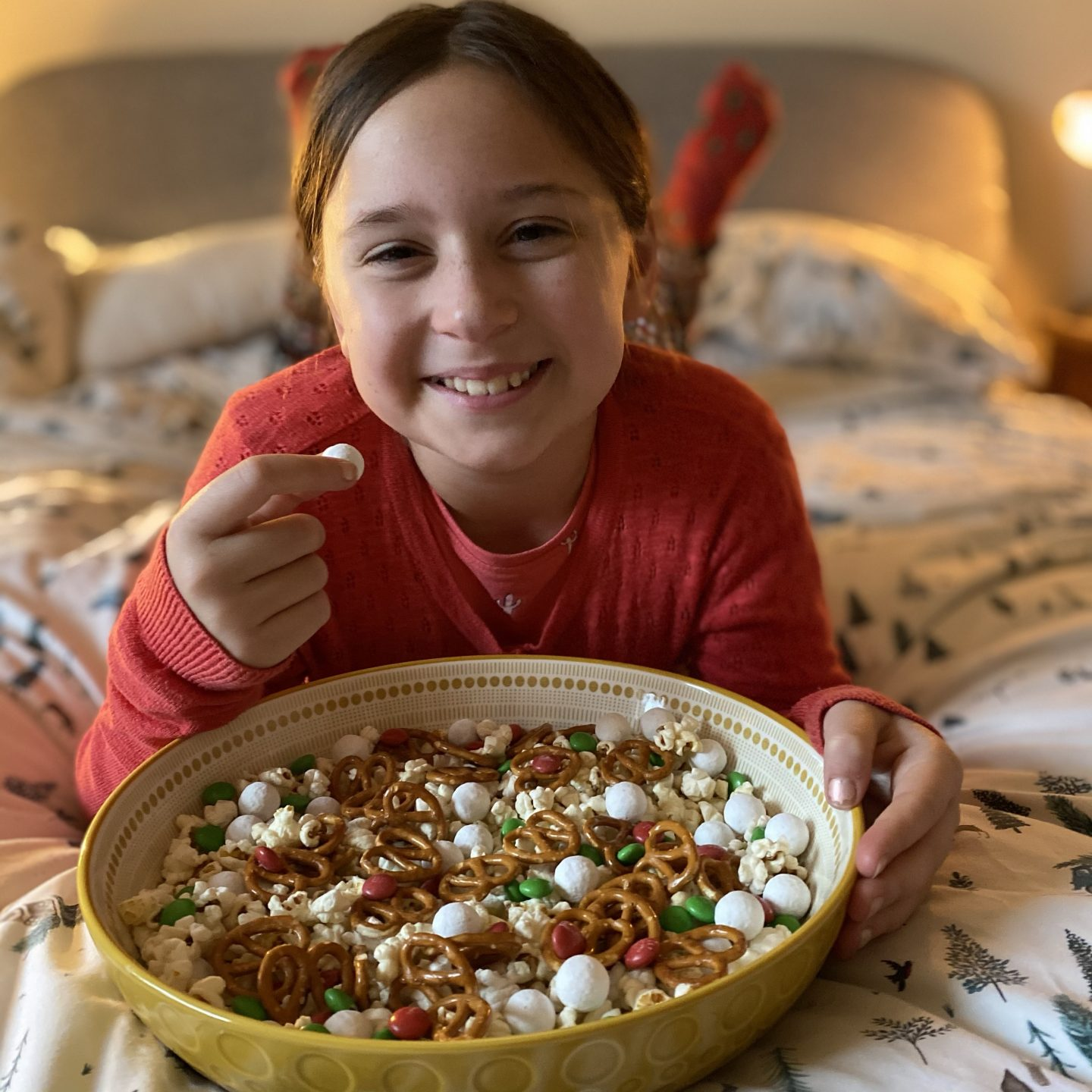 A young girl eating popcorn and snacks on a bed