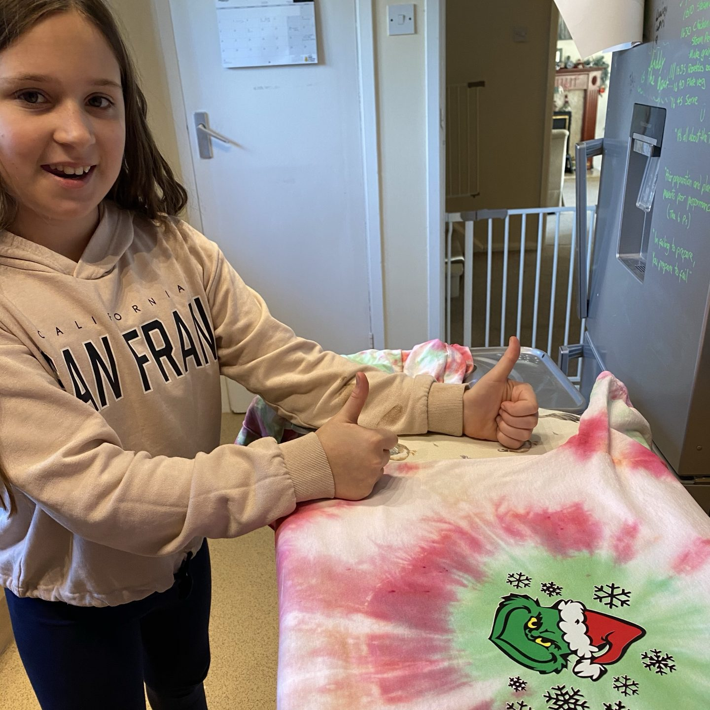 A young girl by ironing board with her tie dye top