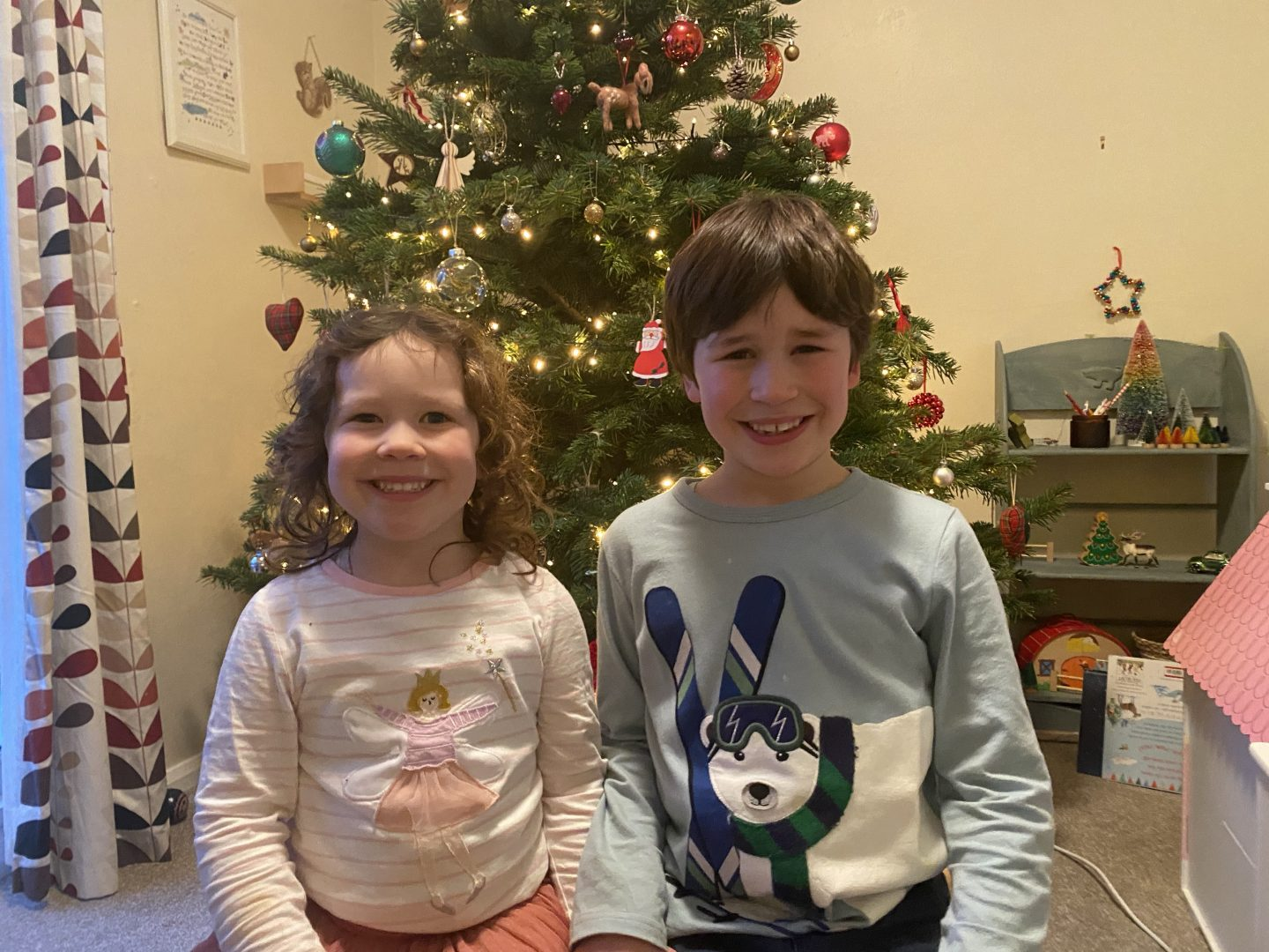 Two children say by the Christmas tree