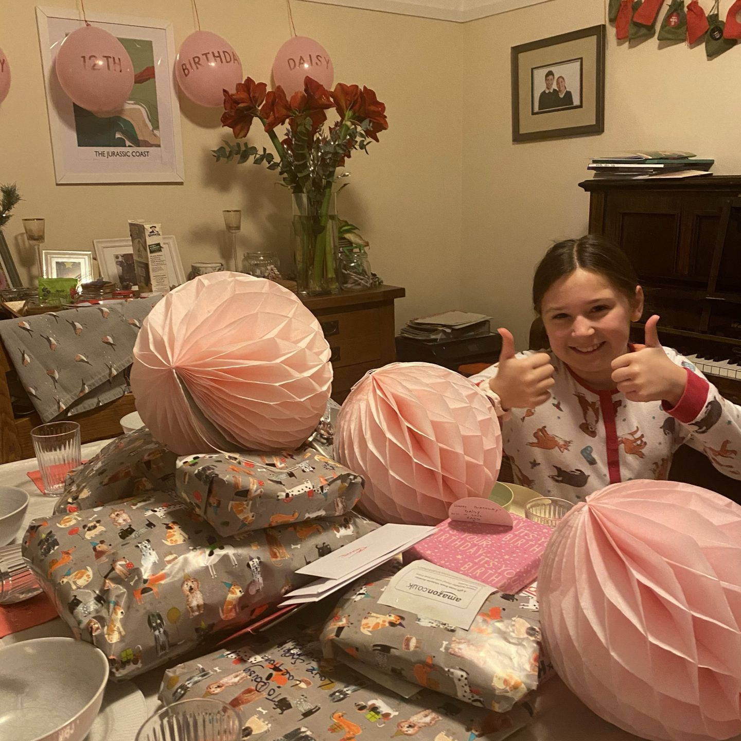 A girl smiling on her Birthday next to presents