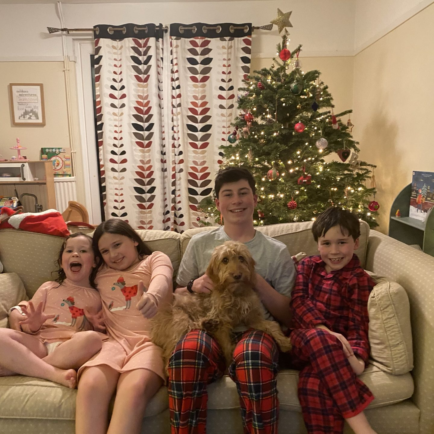 Christmas Eve photo on the sofa with 4  children in pjs smiling