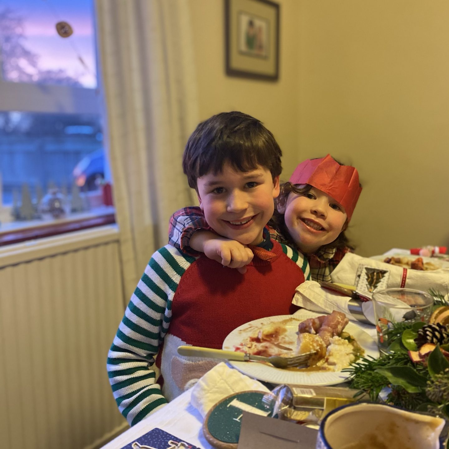 Two children smiling on Christmas   Day with party hats on
