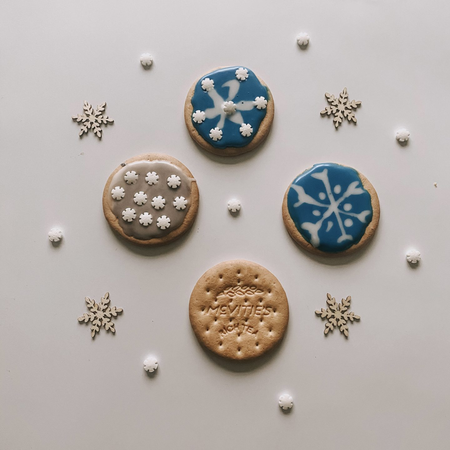 iced biscuits with blue icing and snowflake sprinkles
