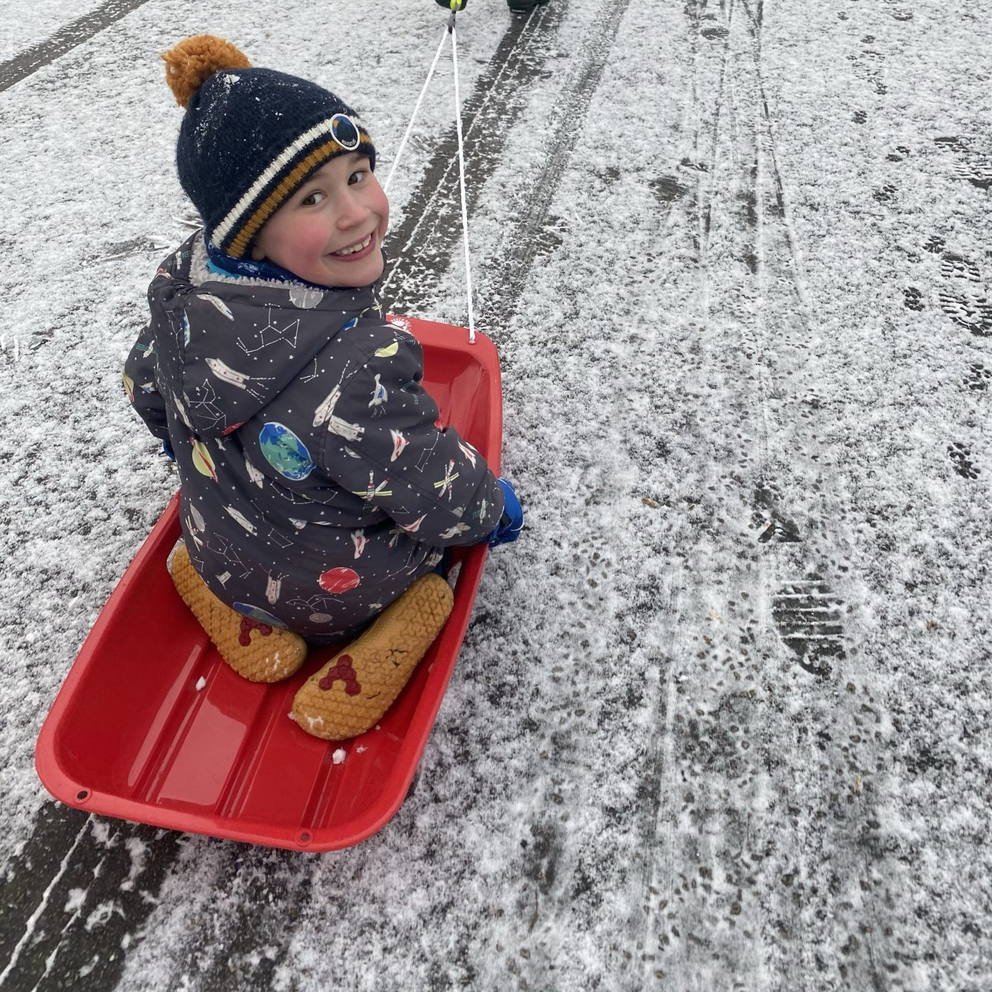 a young boy looking happy on a sledge