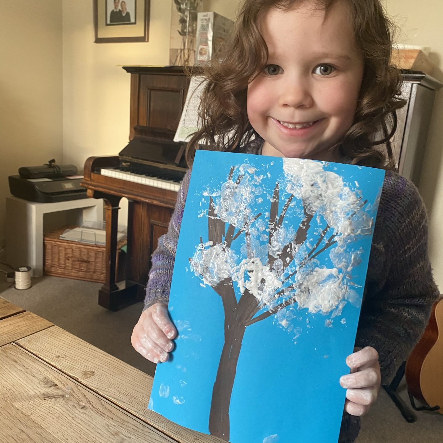 a child smiling with a painting of a snowy tree