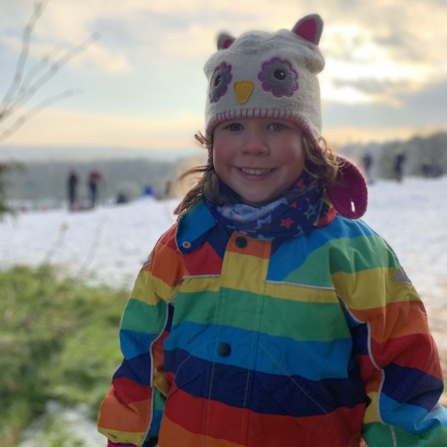 Lockdown in January with a young girl having a snow day and smiling on a snowy hill