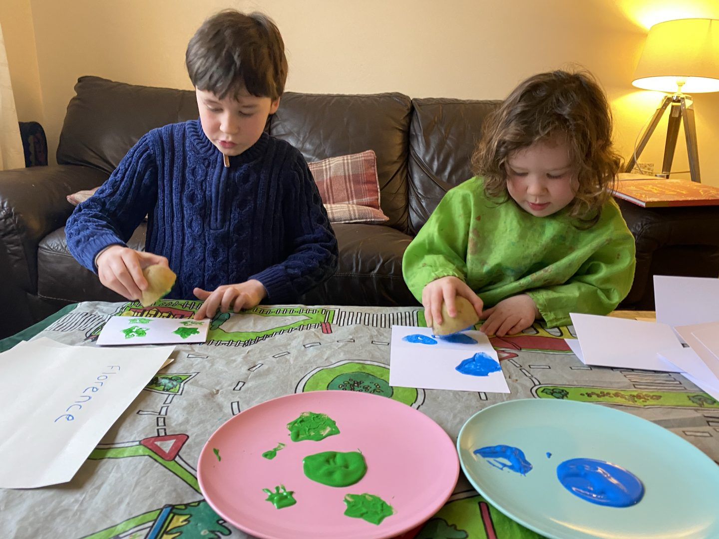 two children painting with potato stamps at a table