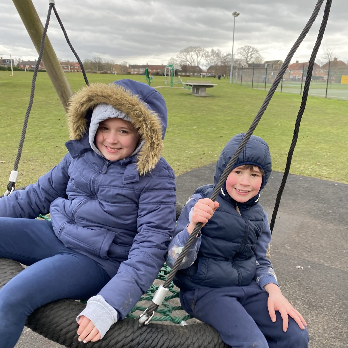 Playground trip with 2  children on a flying saucer swing