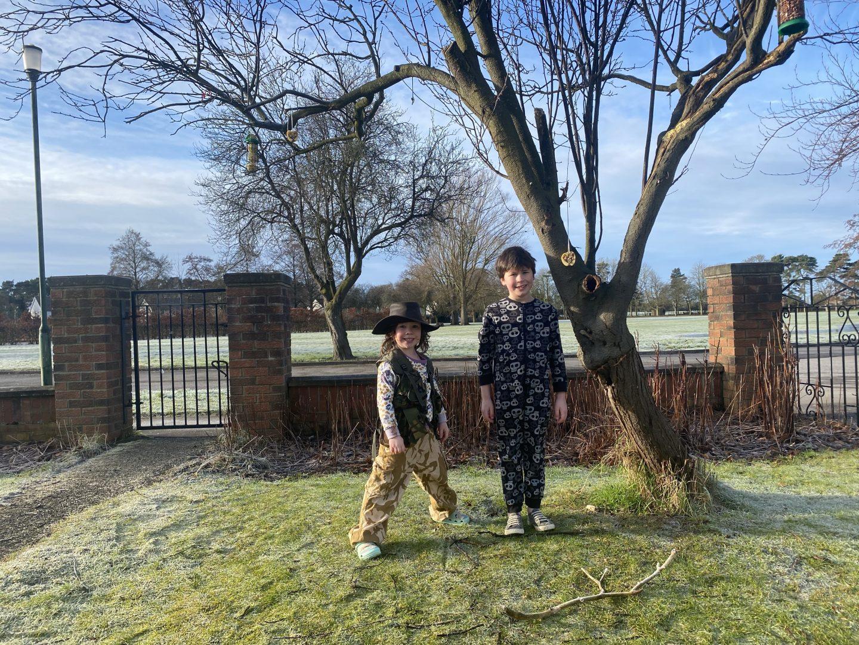 RSPB garden birdwatch with 2 children stood by a tree with bird feeders