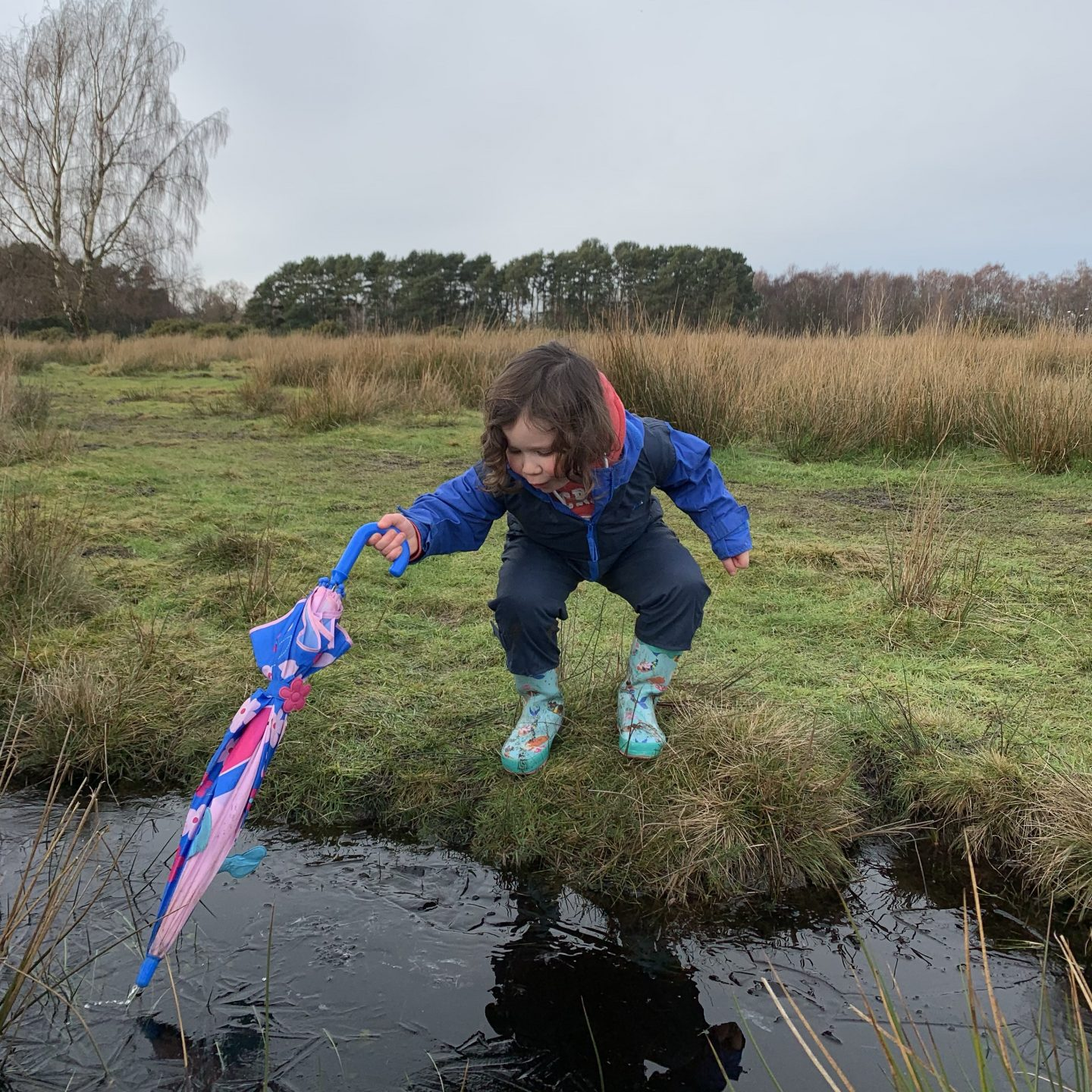 a young girl poking an umbrella in a ditch