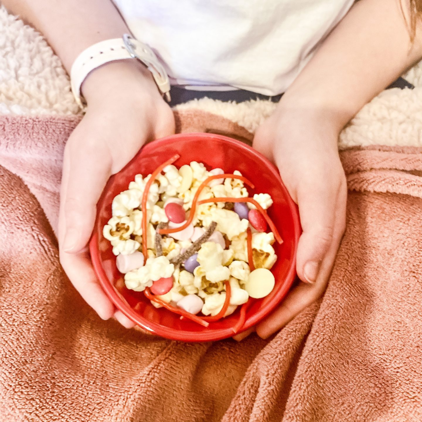 valentine's movie snack mix with a girls sat holding a bowl of movie snacks with popcorn and sweets