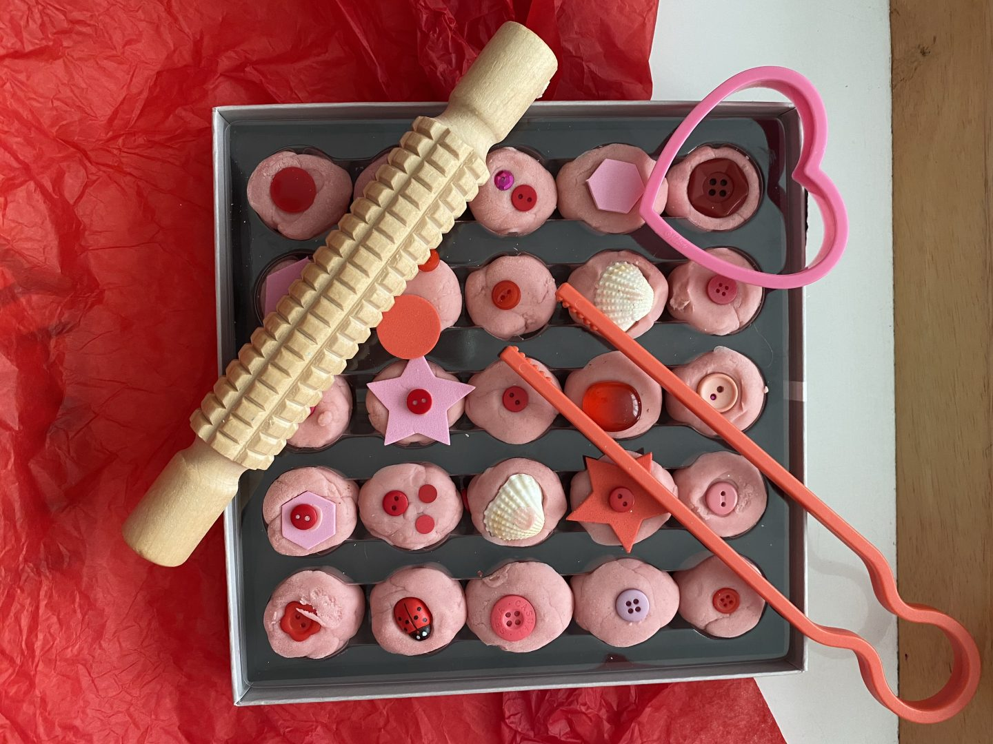 February activities for kids with a box of valentines Playdough chocolates with rolling pin, cookie cutter and chopsticks