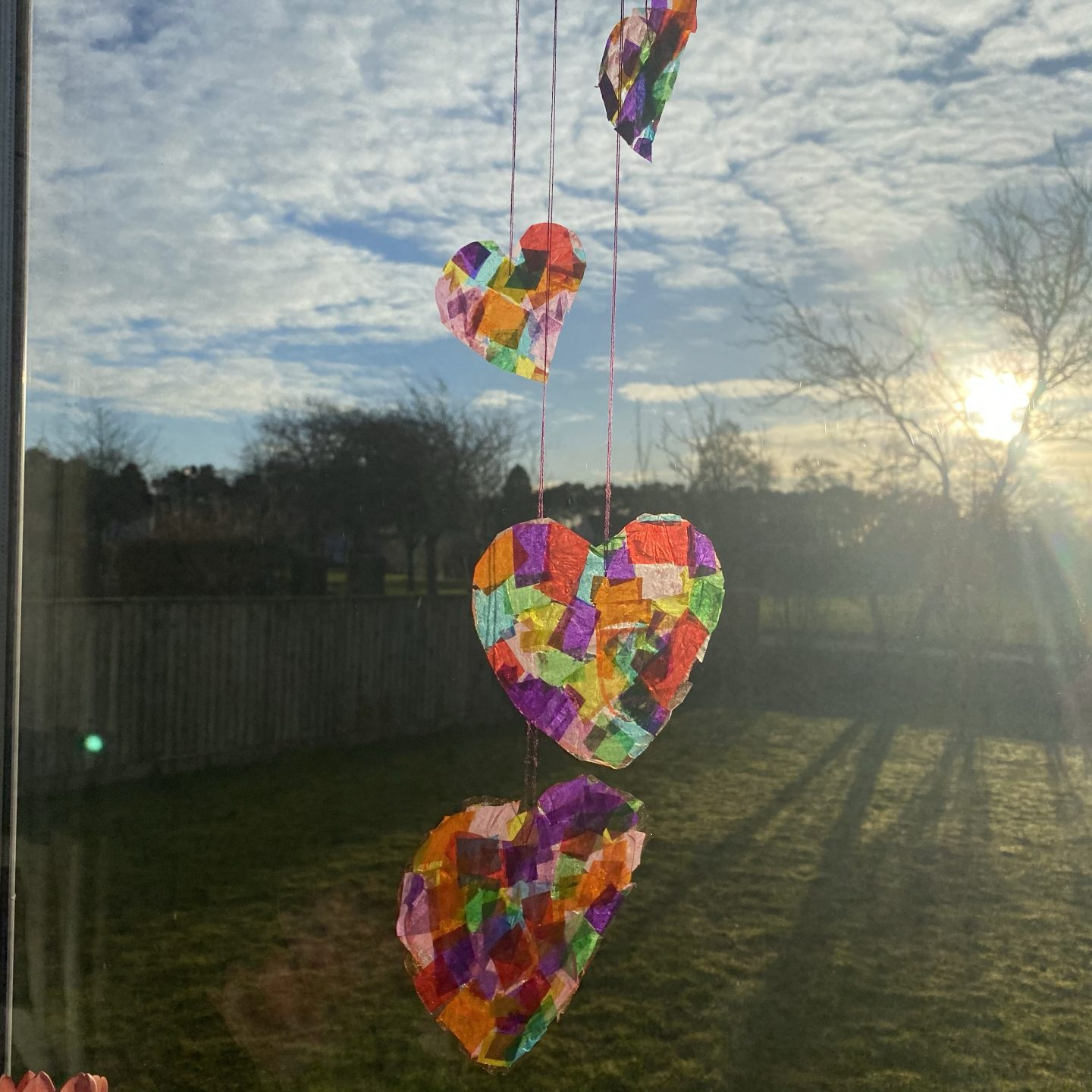 February activities for kids with a rainbow coloured heart shaped sun catcher hanging in the sunny window.