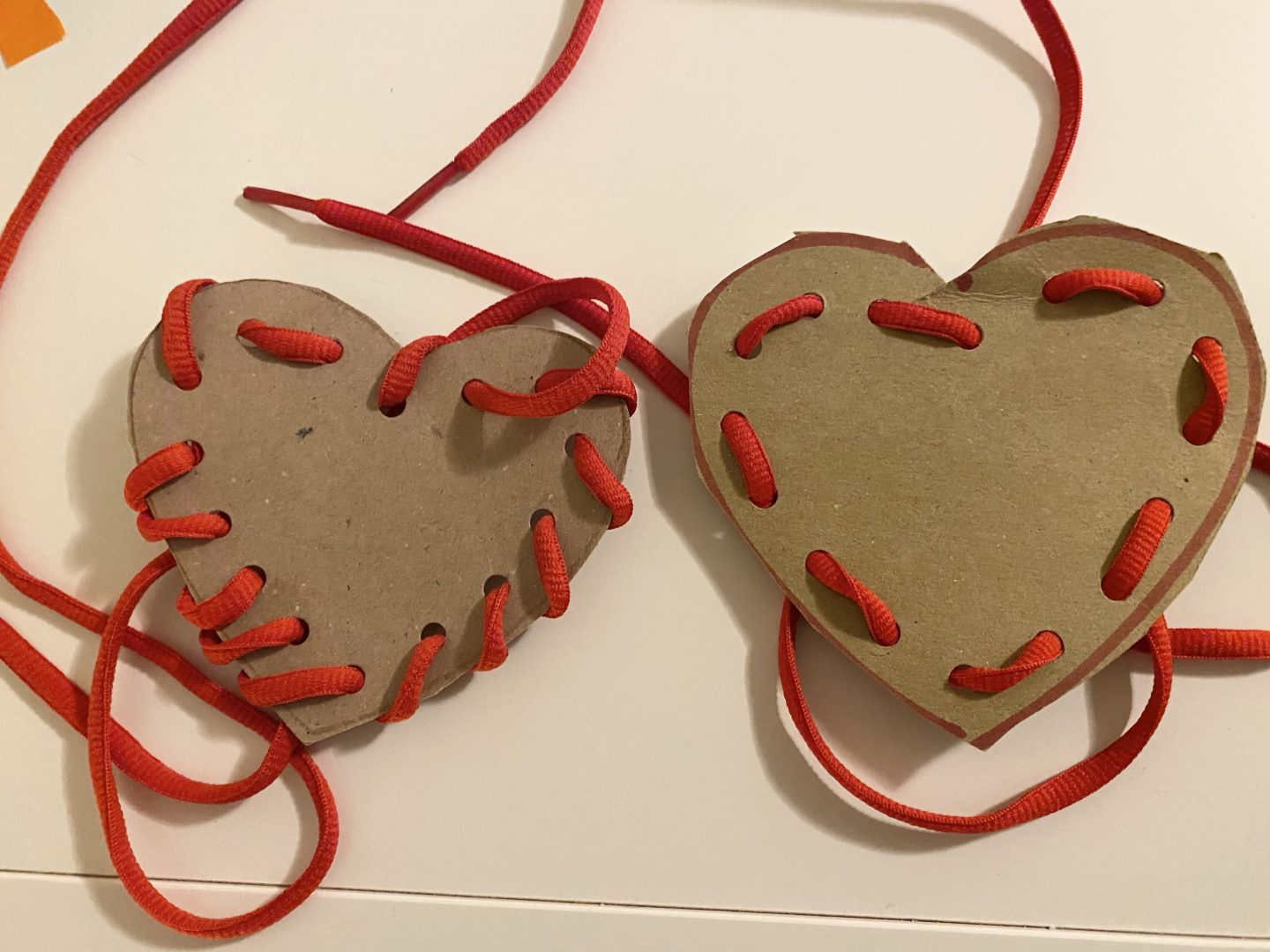 February activates for kids with 2 cardboard shaped hearts with red shoelaces threaded through holes
