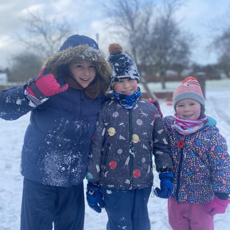 3 children sledging in the snow