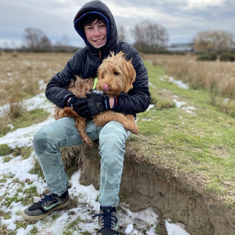 a teenage boy sat on a walk  with his dog